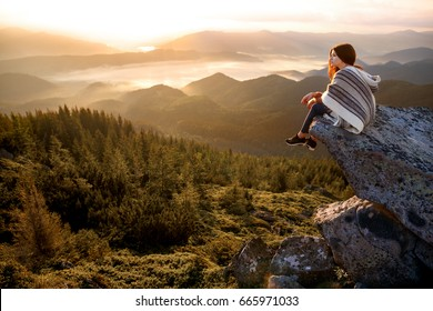 Wonderful landscape with cloud inversion. Relaxing, feeling alive, breathing fresh air, got freedom from work, calm and dreaming Sea of clouds. Hiker relaxing on top of a mountain and enjoying sunrise