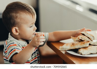 Wonderful little child eating a samosa, puff with meat or qubit