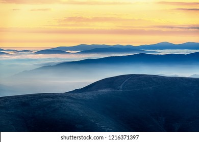 Wonderful morning high in the mountains with clouds below the mountain tops in the valleys. Colorful wild nature landscape