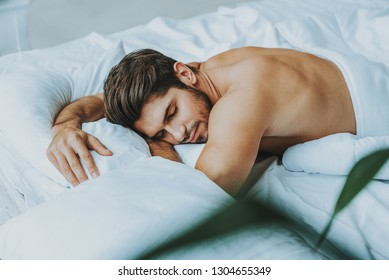 Wonderful morning and relaxation. Waist up portrait of muscular handsome man laying on stomach in bed and having nap embracing the pillow