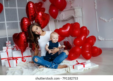 A wonderful mother and baby surrounded by gifts and balloons in the shape of a heart