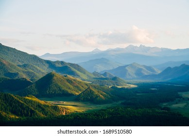 Wonderful mountain land with forest and small houses in sunlight. Scenic view to vast expanses of rolling hills and great mountain ridge on horizon. Immense distances of wavy relief in evening light.
