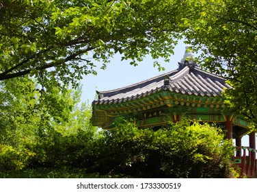 """a wonderful Pavilion of Korean Traditional seen behind the trees The letters written on the wooden board mean """"Maebongsan Mountain pavilion""""."""