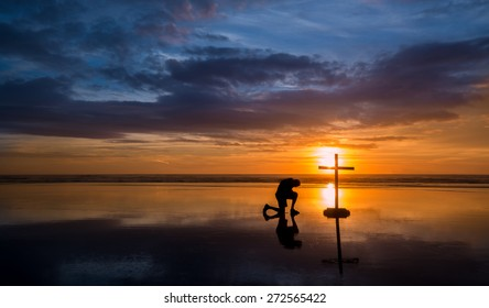 Wonderful reflection on a beach at sunset, with a man kneeling by it.