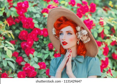 Wonderful retro girl in mint dress on beautiful summer background. Stylish woman. Fashionable summer clothes. Young luxury redhead model with wonderful hairdo on background of bush of roses.