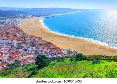 Wonderful romantic afternoon aerial landscape coastline of Atlantic ocean. View Nazare beach riviera(Praia da Nazare) with cityscape of Nazare town in low season at sunny weather. Portugal.