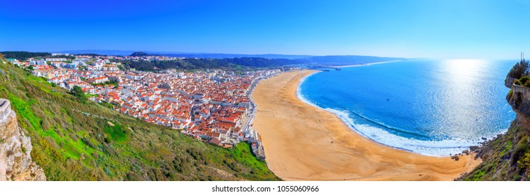 Wonderful romantic afternoon panoramic landscape coastline of Atlantic ocean. View Nazare beach riviera(Praia da Nazare) with cityscape of Nazare town in low season at sunny weather. Portugal.
