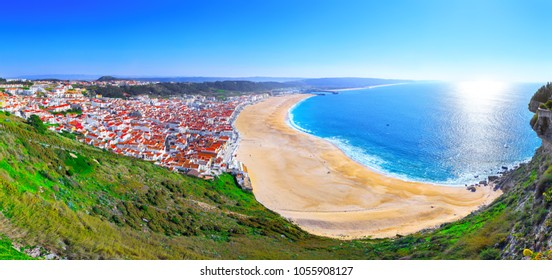 Wonderful romantic afternoon panoramic landscape coastline of Atlantic ocean. View Nazare beach riviera (Praia da Nazare) with cityscape of Nazare town in low season at sunny weather. Portugal.