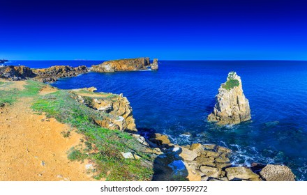 Wonderful romantic afternoon panoramic seascape. Sea birds cormorants resting on a rock. Coastline cliffs of the Atlantic ocean in Peniche. West coast of Portugal at sunny weather.