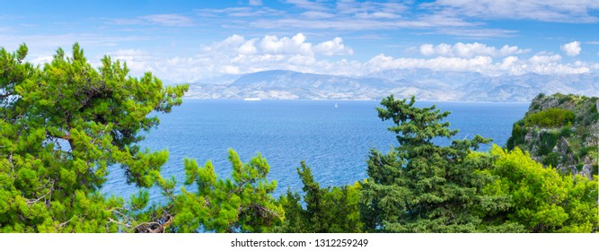 Wonderful romantic summertime panoramic seascape. Sailing yacht with white sails in to the crystal clear azure sea against coastline slopes.