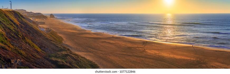 Wonderful romantic sunset panoramic landscape coastline of Atlantic ocean. View Mirante beach in Santa Cruz in low season at sunny weather. Fishermen catch fish. People are walking. Silveira. Portugal