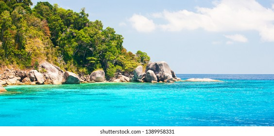 Wonderful scenery of Similan Islands on sunny summer, picturesque crystal turquoise seawater against tropical islands, white clouds and blue sky in backgrounds. Mu Ko Similan National Park, Thailand.