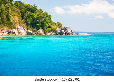 Wonderful scenery of Similan Islands on sunny summer, picturesque crystal turquoise seawater against green island, white clouds and blue sky in backgrounds. Mu Ko Similan National Park, Thailand.