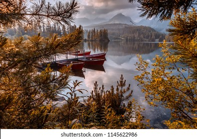 Wonderful Scenic Image. foggy sunny Landscape over the Strbske Pleso Lake. In High Tatra National Park. Wonderful Evening Scene with Calm Fairytale Lake and Mountains Peak on Background. autumn scene