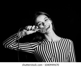 Wonderful sexy woman in white abd black dress with microphone posing on blur background. Karaoke concept
