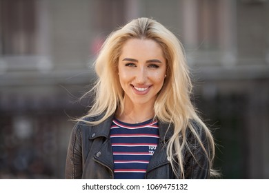 Wonderful smiling blonde woman with a lovely look and bright make up. Natural young beauty. Horizontal shot. Outdoors
