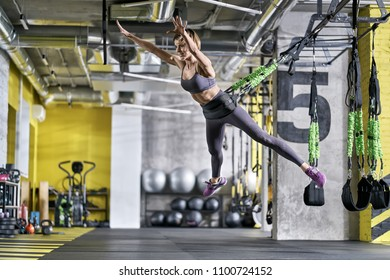 Wonderful smiling girl is training with goflo-trainer in the gym. She is jumping in the air with outstretched arms and legs. Woman wears a gray top and pants, violet sneakers. Horizontal.
