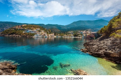 Wonderful summer seascape of Ionian Sea. Wonderful place for holiday. Amazing Greece. Picturesque colorful village Assos in Kefalonia. Turquoise colored bay in Mediterranean sea. Aerial view.