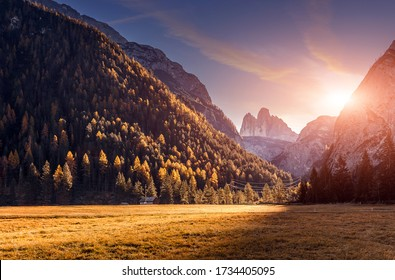 Wonderful Sunny autumn lanscape during sunset. vivid  Morning sunlight on meadow with green grass. Scenic image of wild nature with colorful sky. stunning natural background. Dolomite Alps. Italy.