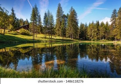 Wonderful sunny landscape in Alps. Scenic image of fairy-tale woodland in sunlit with beautiful reflections in asure water. Amazing nature scenery. Natural background.