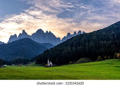 Wonderful Sunny Landscape of Dolomite Alps. St Johann Church, Santa Maddalena, Val Di Funes, Dolomites, Italy. Fairy velley in Dolomites mountains under sunlit. Amazing nature Background.