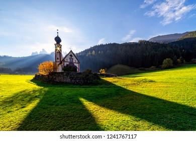 Wonderful Sunny Landscape of Dolomite Alps. St Johann Church, Santa Maddalena, Val Di Funes, Dolomites, Italy. Fairy valley in Dolomites mountains under sunlit. Amazing nature Background.