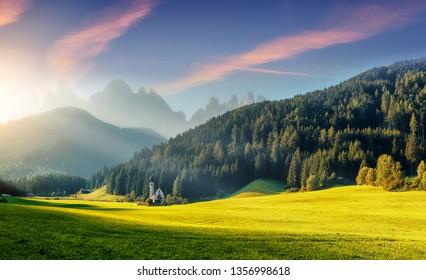 Wonderful Sunny Landscape of Dolomite Alps. St Johann Church, Santa Maddalena, Val Di Funes, Dolomites, Italy. Fairy velley in Dolomites mountains under sunlit. Amazing nature Background. Epic Scenery