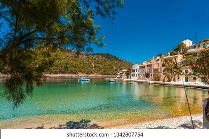 Wonderful Sunny seascape. boats  in beautiful turquoise ocean near an island. Amazing Coastline with Colorful Houses under sunlight.Wonderful morning seascape of Ionian Sea. Assos. Kefalonia. Greece