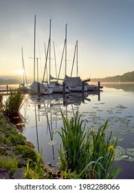 A wonderful sunrise over Lake Baldeneysee in the city of Essen. Moored sailboats in the foreground. Landscape photography
