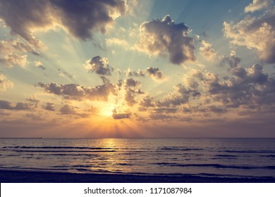 Wonderful sunrise over the sea with golden sun, clouds and light rays