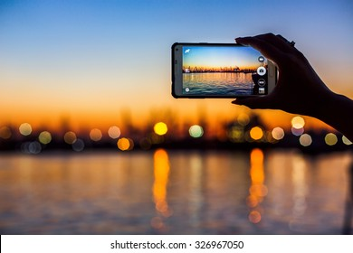 Wonderful sunset over sea harbor, tourist taking a picture of the seaport
