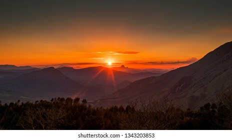 Wonderful Sunset view above the mountains on a Spring Day, with Red and Orange Clouds