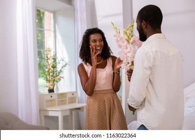 Wonderful surprise. Joyful happy woman smiling while receiving flowers from her husband