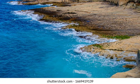 Wonderful turqouise blue ocean water hitting against the rocks - top down view - aerial photography