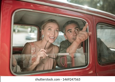 Wonderful view. Amazed smiling married couple seeing the city sights and pointing on them sitting on the backseat of the car.