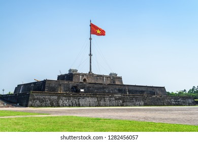 Wonderful view of the flag of Vietnam (red flag with a gold star) fluttering over a tower of the Citadel on blue sky background in Hue, Vietnam. Within the Citadel is the Imperial City.