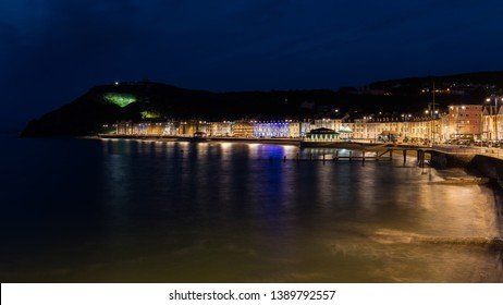 Wonderful view of the night seafront of the illuminated Welsh town of Aberystwyth and the mountain in the background.