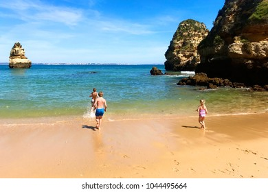 Wonderful view of Praia do Camilo in south of Portugal. Happy children playing, splashing and swimming in the ocean at one of the most beautiful beaches in Lagos, Algarve region.