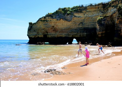 Wonderful view of Praia dos Estudantes in south of Portugal. Happy children playing, splashing and swimming in the ocean at one of the most beautiful beaches in Lagos, Algarve region