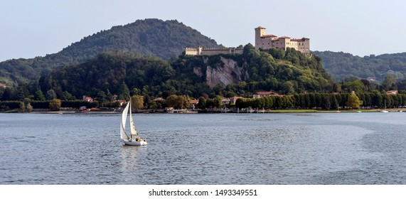 Wonderful view of the Rocca di Angera with a white sailboat sailing on Lake Maggiore, Italy nearby