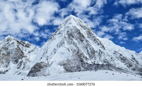 Wonderful view of snow covered Pumori mountain, located on the Nepal-Tibet border (Mahalangur section of Himalayas) and situated 8 kilometres west of Everest, blue sky with white clouds background