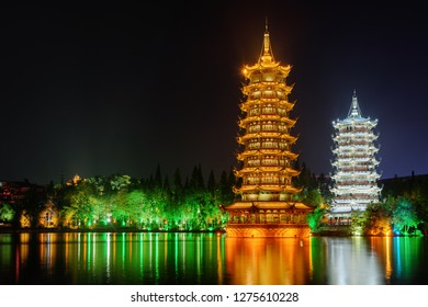 Wonderful view of the Sun and Moon Twin Pagodas at Shanhu Lake (Fir Lake) at night. Gold and Silver Pagodas illuminated at downtown of Guilin, China. Guilin is a popular tourist destination of Asia.