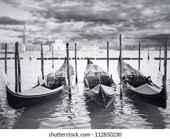 Wonderful view of three gondola parking in Grand Canal with the island with -Basilica of Virgin Mary of Good Health- and dramatic sky on the background in black and white