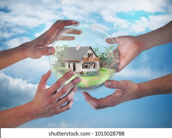 Wonderful village house in a glass transparent ball. The sphere hold many human hands. The background of blue sky. The concept of home insurance, mortgage
