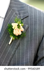 Wonderful wedding boutonniere on a costume of groom from beautiful colorful flowers.
