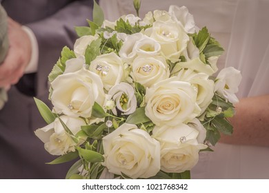 Wonderful white wedding flowers with many jewels and roses. The beautiful flowery accessory of the bride when she will marry her groom. Beautiful decoration. Gratulation in the background