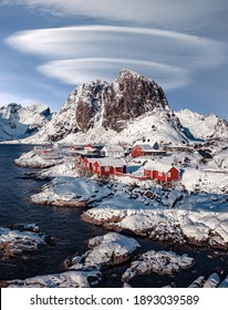 Wonderful wintry landscape. Impressive Winter scenery with Snowcapped mountain, traditional red fishing huts, rorbu and gorgeous sky with fairy tale clouds. Hamnoy village of an ideal resting place.