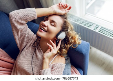 Wonderful woman with curly short hairs listening favorite music, relaxing on sofa. Wearing  cute pink  loungewear.