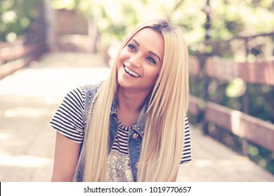 Wonderful young girl with long fair hair relaxing in park posing on bridge and laughing sincerely looking away.