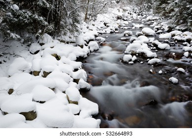 Wonderfull mountain stream in national park West Tatras, Slovakia. Early morning light, snowstorm.
